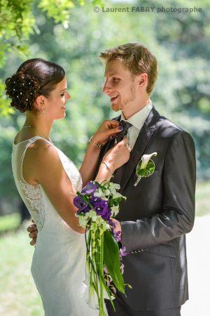 la mariée ajuste la cravate du marié dans le parc de Buisson Rond à Chambéry, photographe en Savoie