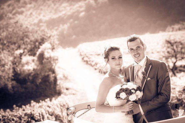 Sourire des mariés debout dans leur voiture, traitement d image rose sépia, mariage en Savoie