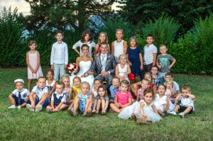 tous les enfants sont rassemblés pour une photo de groupe avec les mariés