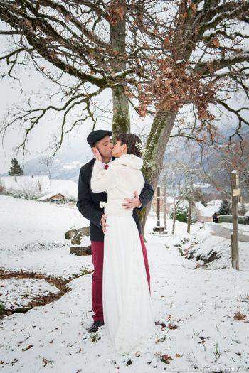 Le baiser des mariés près d un banc enneigé sous les arbres en hiver : photographe mariage Savoie