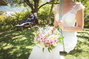 sur une idée de leur photographe, la mariée pose sur la balançoire pendant que le marié se repose sur un transat