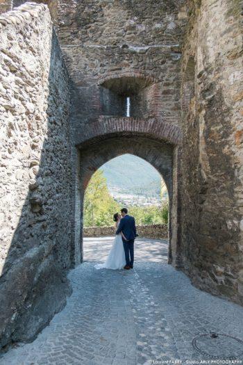 les mariés passent la porte Sarrasine dans la cité médiévale de Conflans, en Savoie (photographe Albertville, 73)