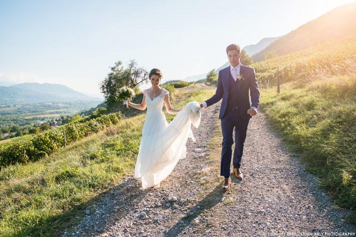 les mariés avancent vers le photographe lors de leur séance photo de couple par une belle lumière en contre-jour